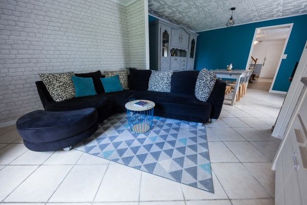 Photo of the dining room with a dark blue sofa, turquoise and light blue cousins, behind a repainted wooden buffet and a turquoise wall