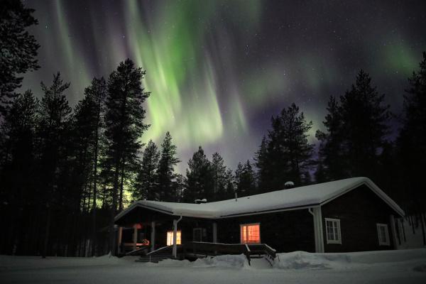Maison dans la nuit avec le toit recouvert de neige, les lunières allumées et au dessus des sapins une belle aurore boréale