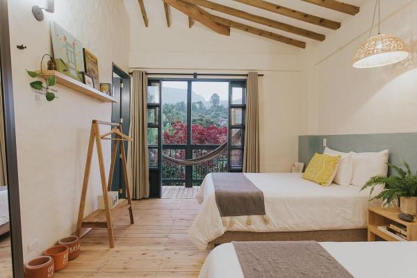 Photo prise dans une chambre à la décoration moderne et épurée. Il y a 2 grands lits et la baie vitrée ouverte donne sur un balcon où on aperçoit un hamac.
