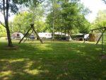 Aire de jeu du camping sous les arbres avec des balançoires en bois. Au fond on voit des caravanes et une tente
