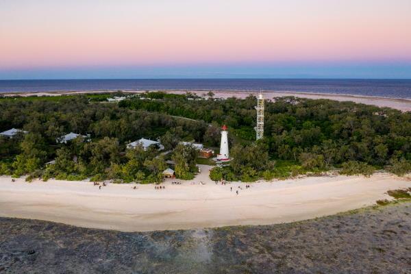 Vue du ciel au soleil coouchant on voit la mer, la plage et la végétation ou sont cacahés les logements ainsi que le phare de l'ile qui surpasse tout cela
