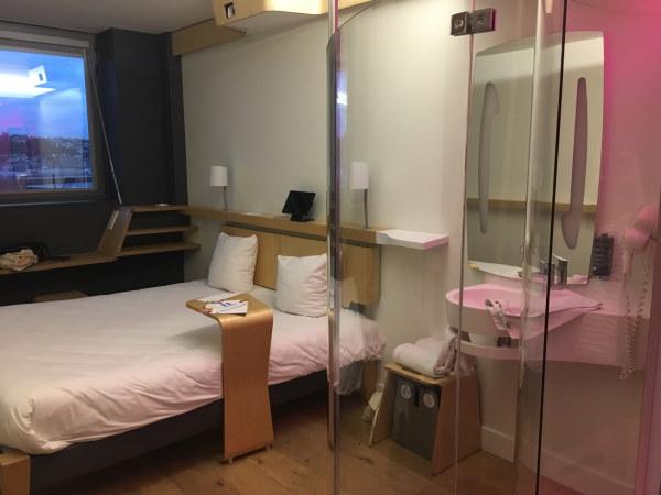 Photo de la chambre prise depuis la porte d'entrée avec sur la droite la douche et devant le lit double et la fenetre