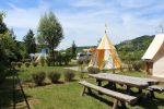Photo prise dans le camping avec une table de pique nique en bois et une tente orange et jaune derrière