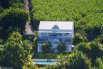 Vue du ciel la maison de 3 étages à l'architecture typique de la réunion de couleur blanche et bleue. Autour de la végétation luxuriante et devant la piscine