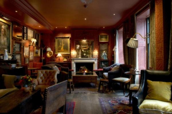 Intérieur du salon de l'hôtel avec une décoration très cosy british avec de gros fauteuil et une cheminée allumée au fond de la piece