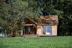 Photo d'un des lodge en bois avec une grande baie vitrée. A sa gauche un grand chene et devant une belle pelouse verte
