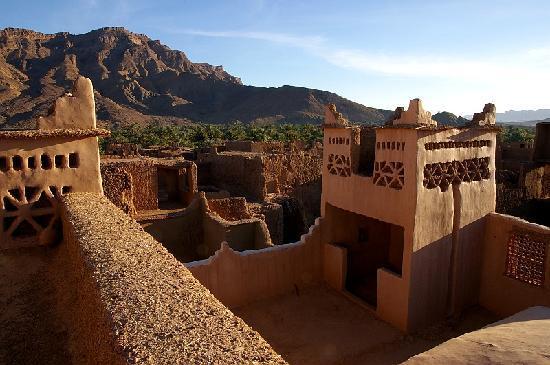Photo prise du le toit de la Kasnah on peut y voir la cour intérieure ainsi qu'une partie du batiment en architecture traditionnelle. Au font on aperçoit les montagnes