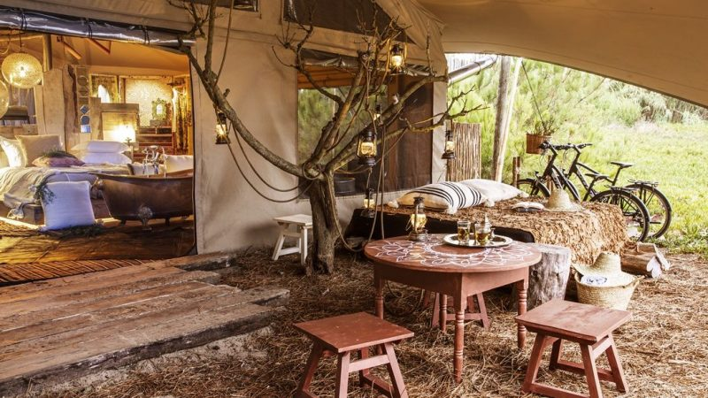 Photo prise sur la terrasse couverte d'une des tentes de glamping. On voit une table basse avec tabouret en bois, un espace pour faire une sieste et au fond la chambre avec la baignoire ancienne au milieu de la pièce.