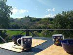 Table dressée pour le petit dejeuner sur la terrasse exterieure avec une vue dégagée sur la campagne vallonée