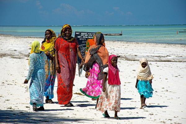 Zanzibar - Femmes et enfants vetus de tissus colorés sur une plage de zanzibar. Sable blanc et eau turquoise
