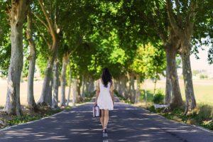 Femme avec une robe blanche, portant une petite valise. Elle est de dos et en marche au mieu d'une route entourée de platane