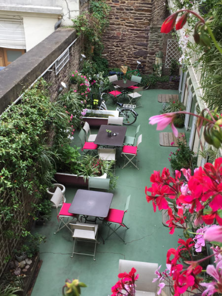 Garden Hotel. Photo du pation prise depuis une des chambres. Patio très fleuri et avec du mobilier dans les ton rose et vert