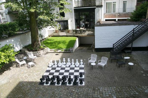 Photo de la cours de l'hotel ensoleillée : murs blancs, petit espace d'herbe, mobilier en fer noir et blanc et grand echiquier au sol avec ses grands pions