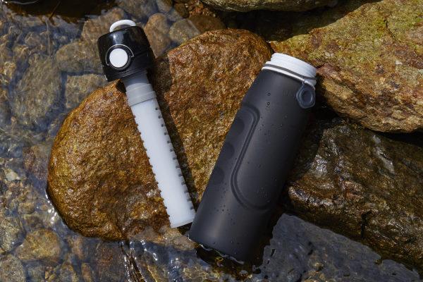 Remplacer les bouteilles en plastique - Photo de la gourde huma green noir et son filtre posé sur un rocher dans une rivière