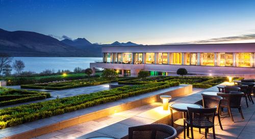 Kerry - The Europe. Photo prise depuis l'une des terrasses de l'hotel à la tombée de la nuit. On y voit le batiment éclaire, le lac et les montagnes et des tables de restaurant pour personnes face à la vue
