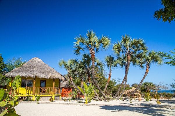 Bungalow en bois jaune vif qui contraste avec le blanc su sable, la vert de la végétation et le bleu éclatant du ciel