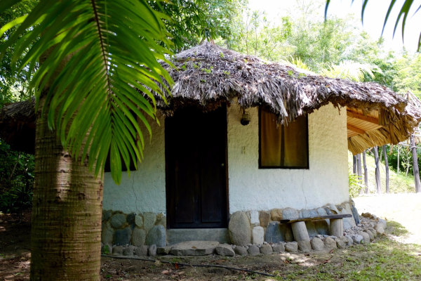 Minca - Reserva Caoba. Photo d'un des bungalow aux murs blanc et toit de paille entouré d'arbres