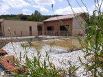 Photo prise dans le jardin au premier plan il y a la piscine et derrière la maison d'hôtes