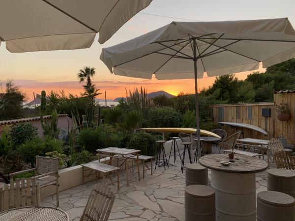 Photo prise sur la terrasse de l'hotel au coucher de soleil avec beaucoup de végétation devant et au fond la mer