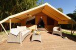 Photo d'une tente de glamping de face de couleur beige avec sa grande terrasse amenagée de bain de soleil