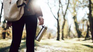 Personne sur un chemin entouré d'arbres et illuminé de soleil tenant dans sa main une gourde en inox
