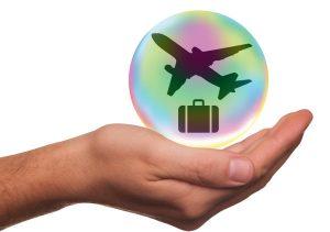 Une main horizontale qui supporte une bulle avec un avion et une valise