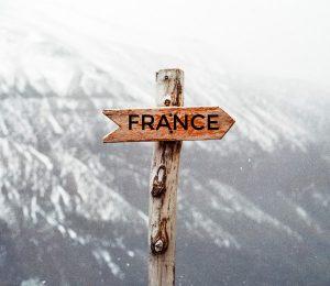 panneau en bois en forme de fleche dans un paysage montagneux enneige avec écrit France dessus