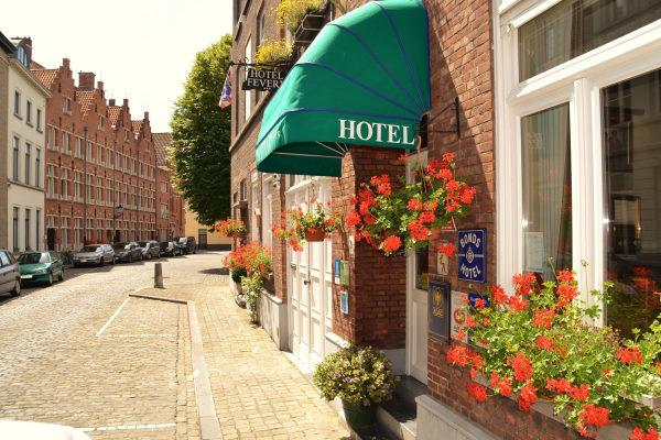 Eco-hôtel Fevery Bruges - Photo de la devanture fleurie avec des murs en briques rouges, des menuiseries blanches et un auvent vert