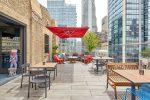 Virgin Hotel Chicago - photo de la terrasse amenagée sur le toit de l'immeubme : un grand canapé gris protégé avec une voile rouge, un table pour 2 et une table plus grande en bois, le tout vue sur les bulding du centre ville