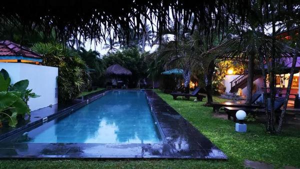 Turtle eco beach - couloir de nage avec un contour noir au milieu d'une pelouse verte et grasse. Autour il y a des transats avec des parasols en paille