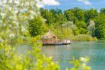 Les grands lacs - cabane en bois sur une plateforme flottante au milieu du lac avec toit en paille