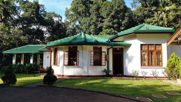 Sweet Cinnamon Kandy - Photo prise dans le jardin du batiment aux murs blancs et toit en tuile vertes.