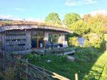 Lackan Cottage Farm - photo du cottage en bois avec toiture vegetale et à côté les panneaux photovoltaïques