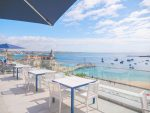 Hotel baia cascais - photo taken from the terrace of the hotel facing the sea. The terrace is furnished along the glass balustrade of the restaurant table and in the background there are deckchairs