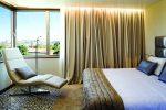 neya-lisboa-hotel - Photo d'une chambre de l'hotel avec une fenetre en angle, un grand fauteuil allongé