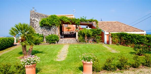 Le Case Di Civi - photo d'une des maison avec une grande terrasse ombragée et devant une grande pelouse verte