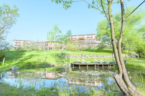 Retter Bio Natur Resort - Photo prise en contre bas devant la piscine naturelle et au dessus on voit les bâtiments de l'hotel derrière les arbres