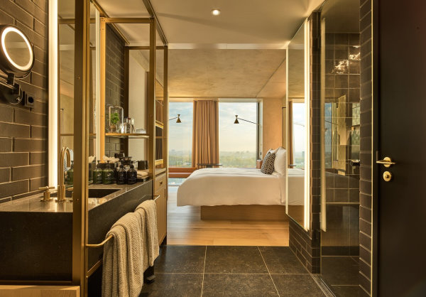 QO - Photo en perspective prise depuis la salle de bain avec la faience noire qui donne directement dans la chambre avec le lit 2 places et 3 grandes fenetres