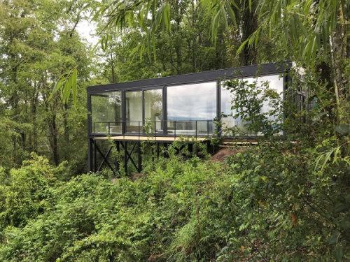 Bâtisse vitrée, grise, entourée de végétations.