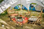Vegan surf camp - mobilier exterieur (chaise en bois, table bobine, chaise de camping) sur un tapis de sol sous un auvent entouré de tentes