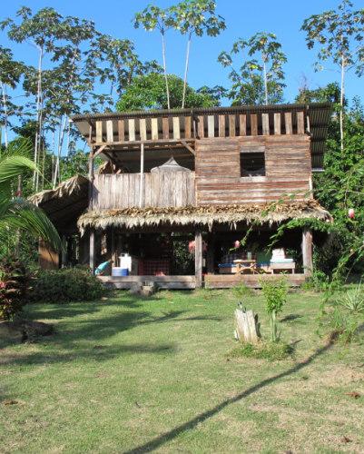 carbet toubo - Photo d'un des batiments en bois. Le rez de chaussé est ouvert et est une terrasse couverte les pièces se trouve au dessus