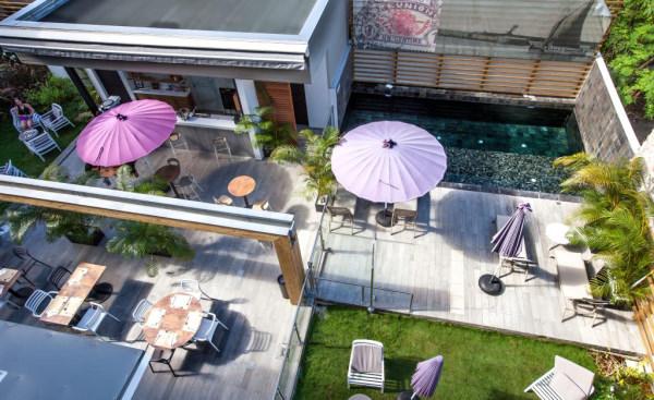 le saint pierre - Photo prise en hauteur du patio interieur avec de la pelouse et avec transat parasol et bar