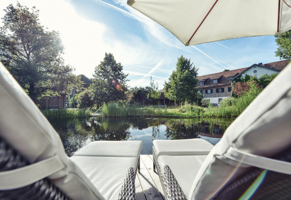 biohotel-schlossgut-oberambach - Photo prise depuis une des rives de l'étang où spnt installés deux transats. De l'autre côté de la rive il y le batiment de l'hotel aux murs blancs et toit en tuiles rouges