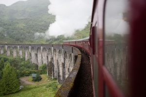 harry potter's famous red steam train on the aqueduct
