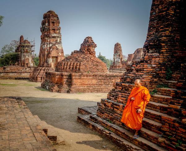 les temples de l'ancienne cité d'Ayutthaya avec un homme habillé en orange