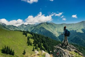 activités ecologiques - randonneur sur une crète surplombant un paysage montagneux spectaculaire. Des sapins recouvrent une coline