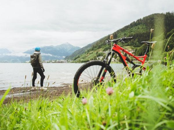 un homme a posé son vélo rouge le long du quai et lui regarde le lac et les montagnes