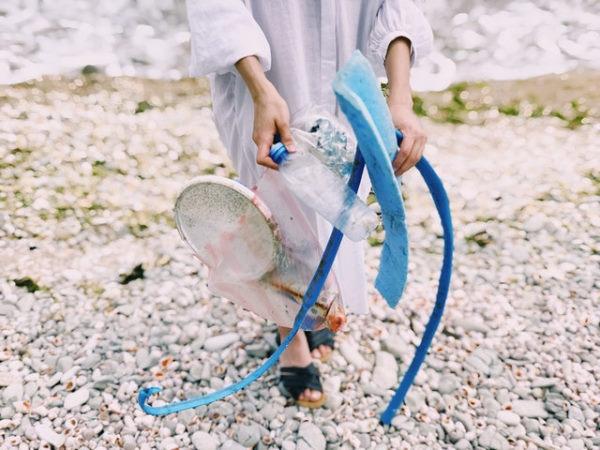 Une femme sur une plage tenant dans ses mains des déchets plastiques qu'elle a ramassé