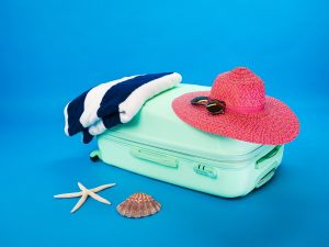 vacances zéro déchet - 6serviette bleue et blanche placée à côté d'un chapeau rose tous les deux posés sur une petite valise