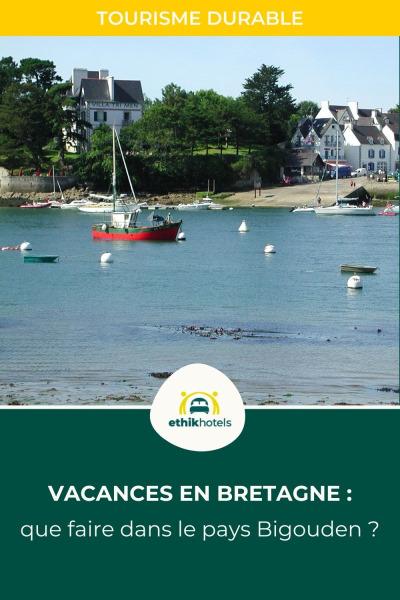 Photo d'annexes et un bateau rouge amarré dans la mer en face d'un village breton